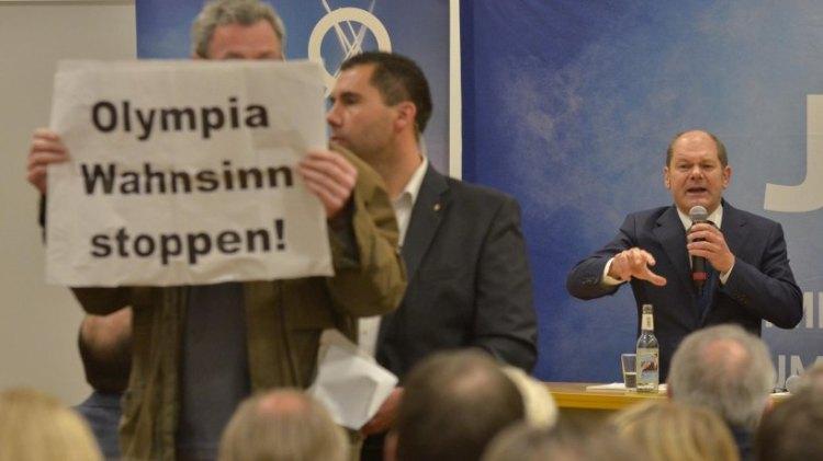 """Un opposant à la candidature de Hambourg brandissant une affiche : """"Arrêtez la folie olympique !"""" (Crédits - Hamburger Abendblatt / Joto)"""