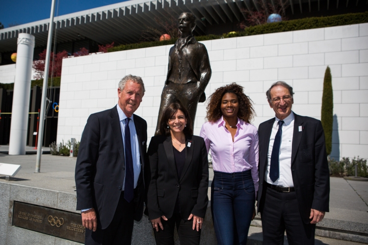 De gauche à droite, Guy Drut ; Anne Hidalgo ; Muriel Hurtis ; et Denis Masseglia devant la statue du Baron Pierre de Coubertin à Lausanne (Crédit - Pierre Aldouy / AFP / Paris 2024)
